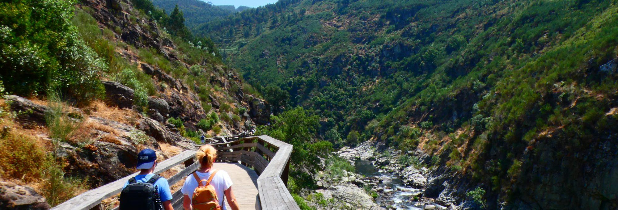 Turistas a caminhar nos Passadiços do Paiva, num dia de sol, com vista sobre o vale do rio paiva. Visita guiada. Tour.